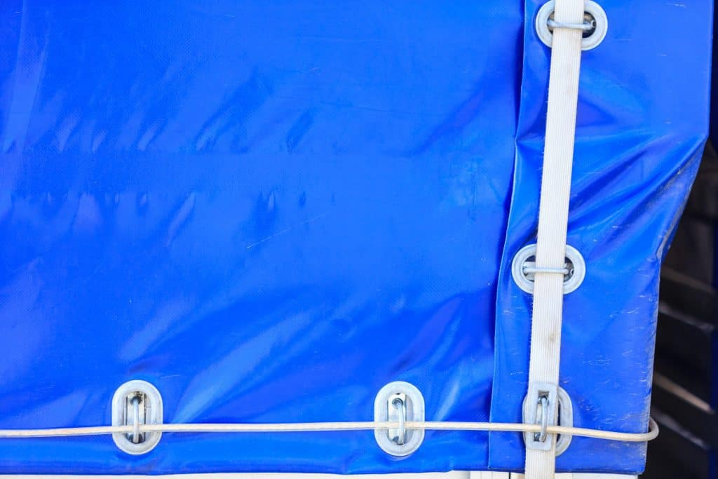 close-up photo of rv cover straps holding blue cover tight
