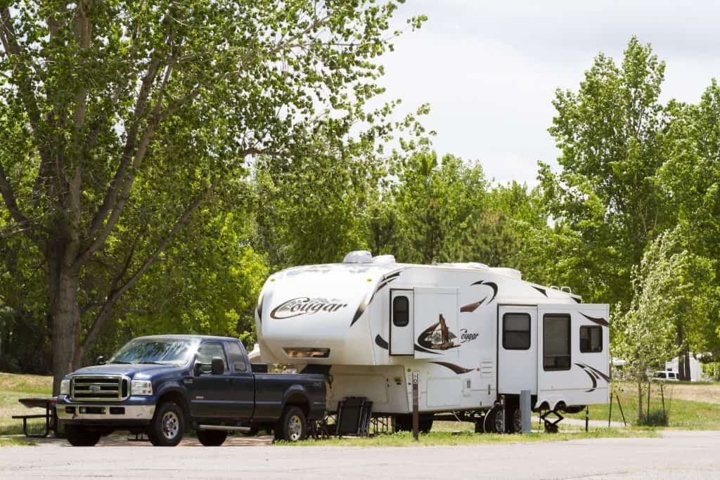 Large 5th wheel and blue truck parked at campground.