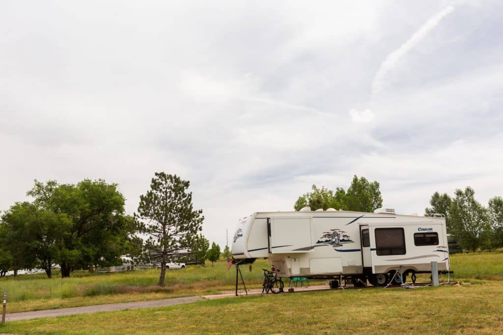 5th wheel parked and connected at an RV campsite.