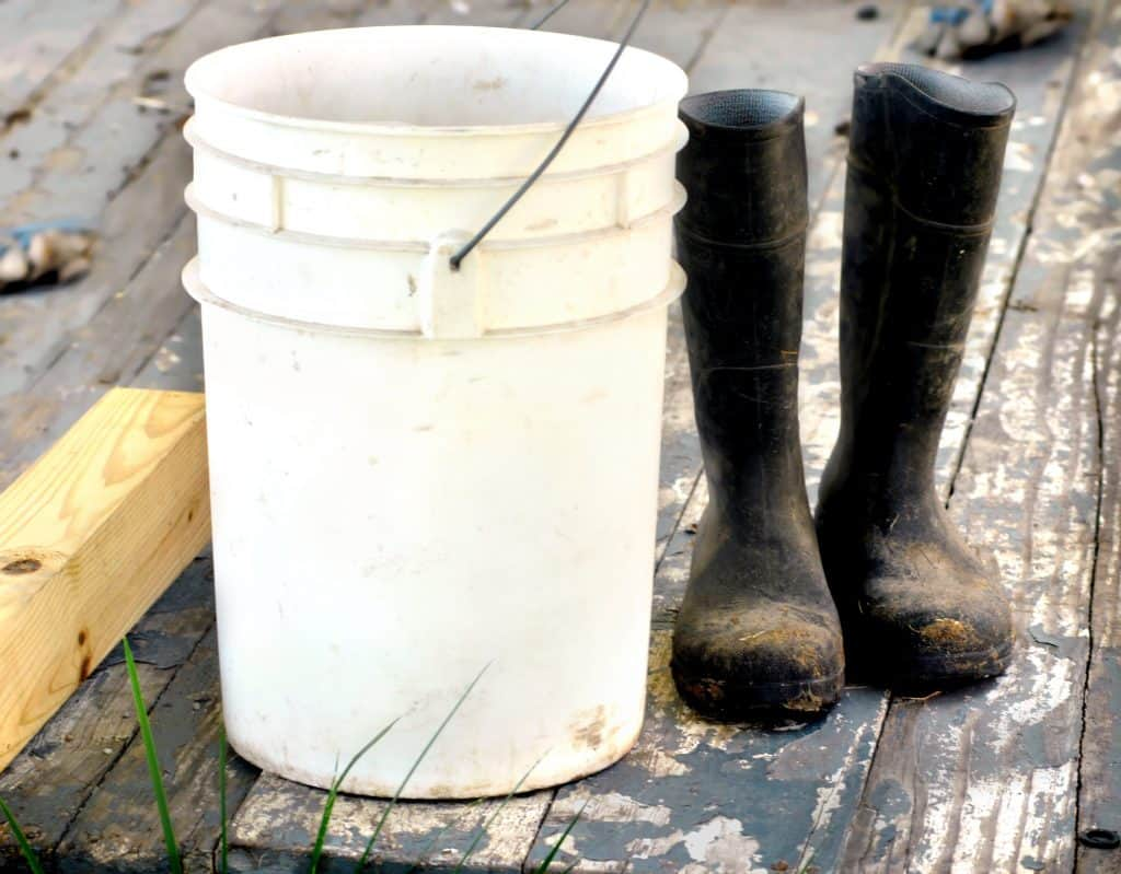 Empty bucket and muddy boots on a deck made of wood.