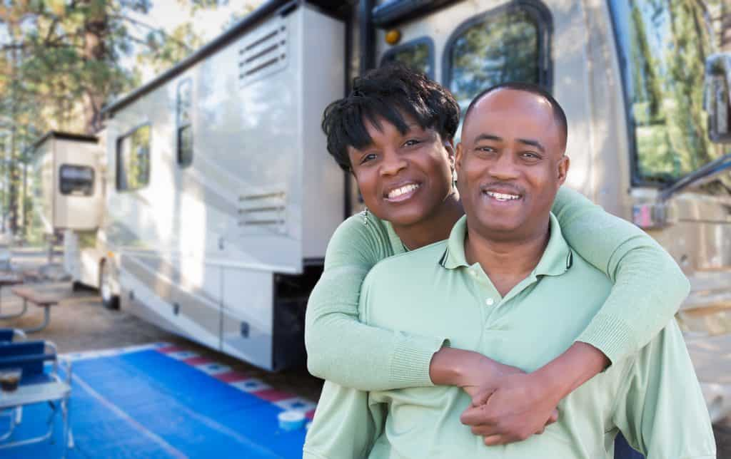 Couple stands outside their motorhome at campsite.