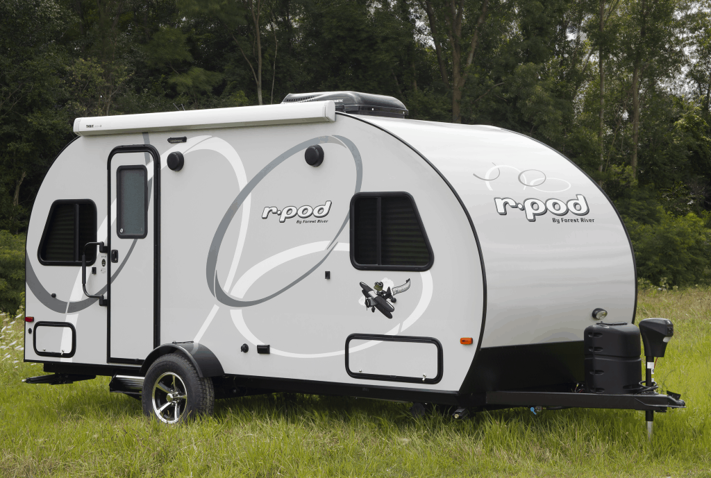 Forest River r-pod sits in lush field at edge of forest.