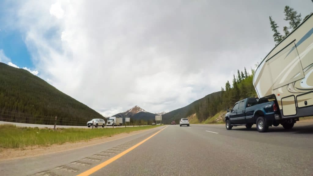 Pickup Truck tows fifth-wheel on scenic highway.
