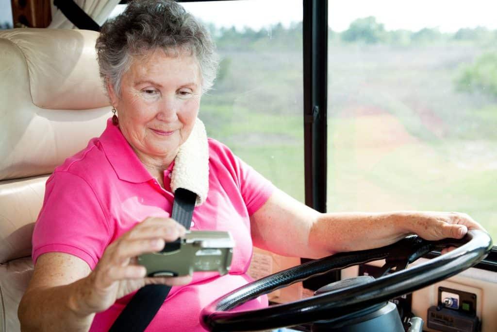 Woman checks GPS while driving large motorhome.