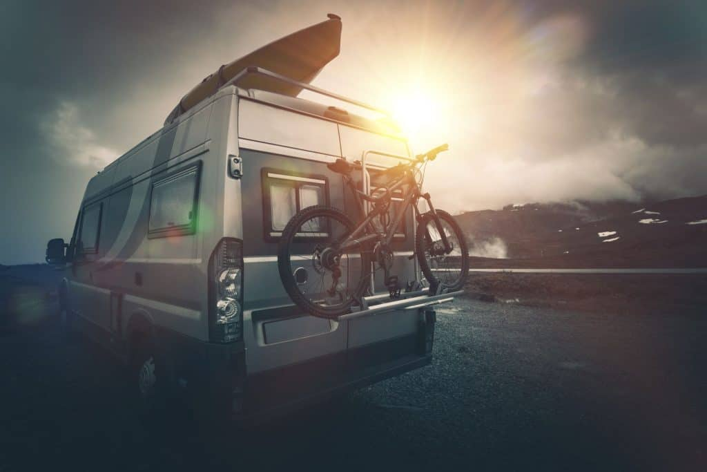 RV with kayak and bike is parked.