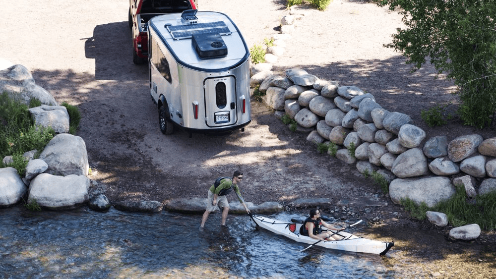 Small airstream travel trailer on boat ramp as kayakers push off.