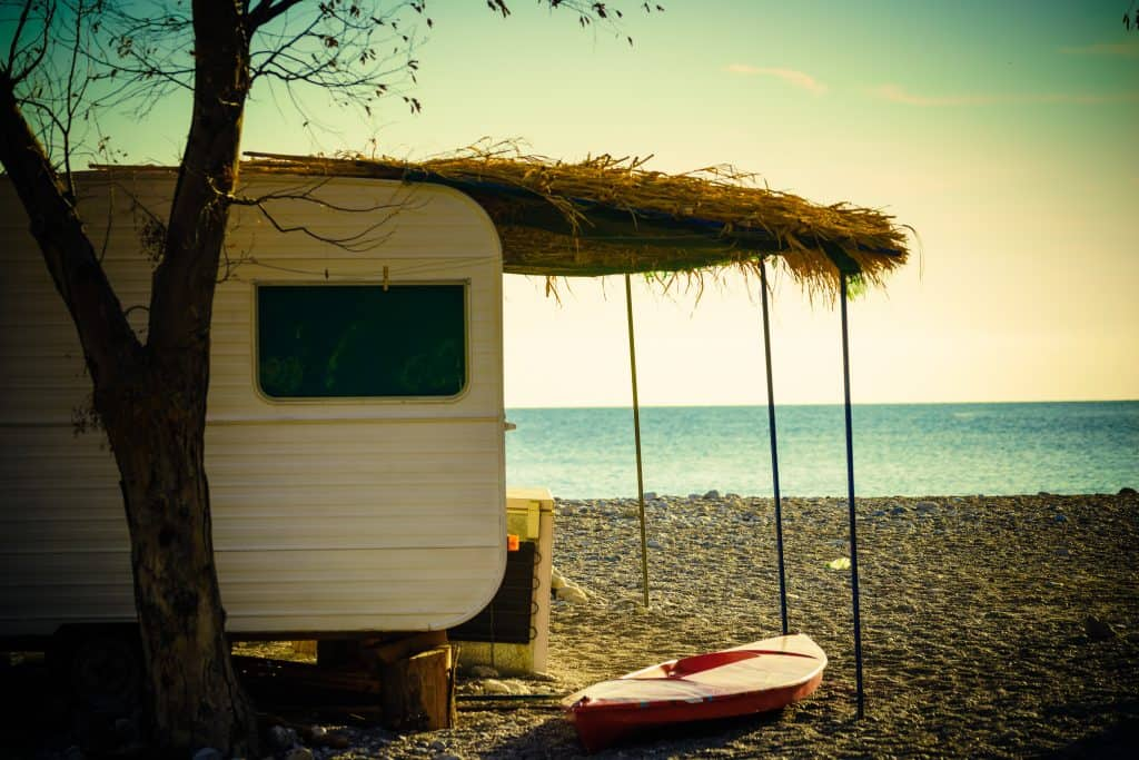 Travel trailer on the beach with grass awning cover.