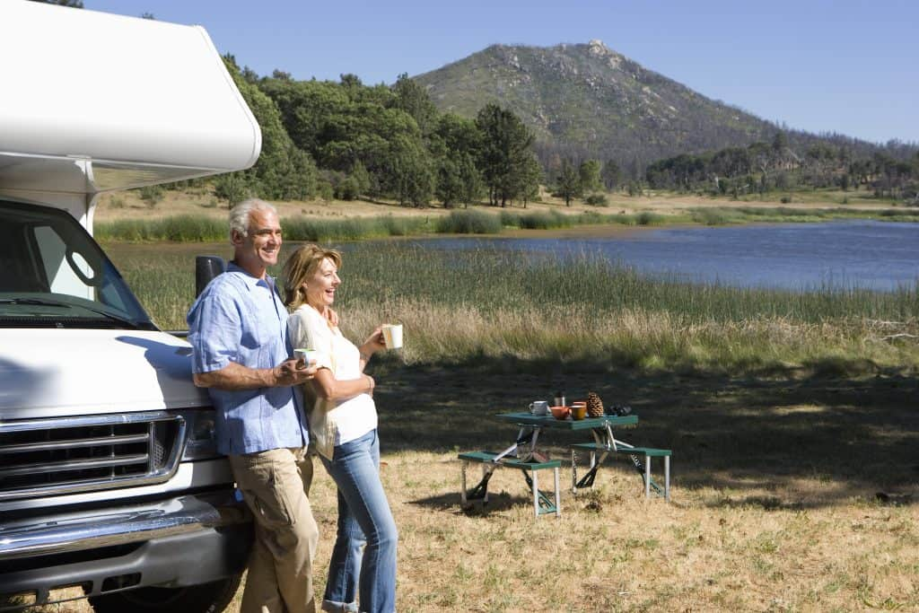 Couple enjoys coffee near their RV parked by a lake.