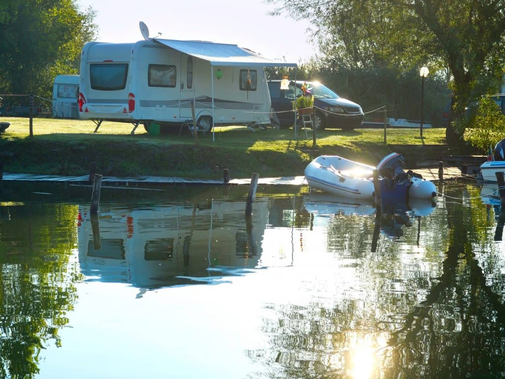 Travel trailer at lakes edge with inflatable motor boat.