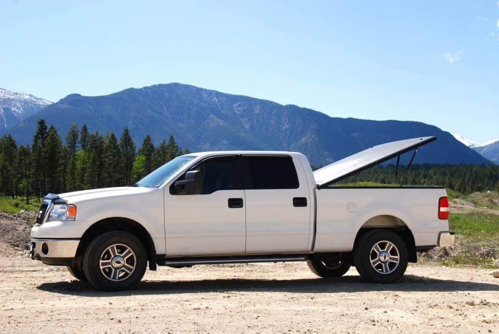 White pickup truck in rugged landscape.