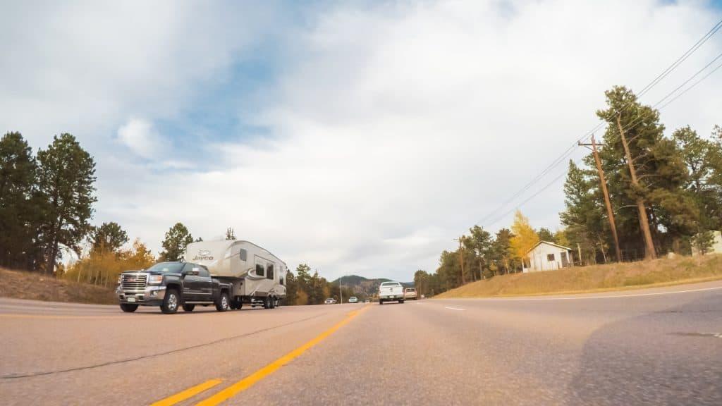 5th wheel being towed on rural highway.