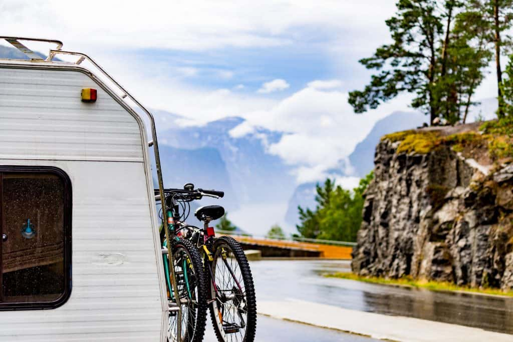 Bicycles attached to the side of a small RV travel trailer.