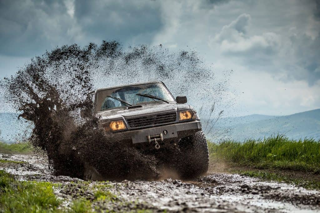 Off road vehicle bounces through muddy trail.
