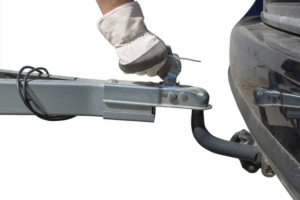 Gloved hand operates trailer hitch mechanism.