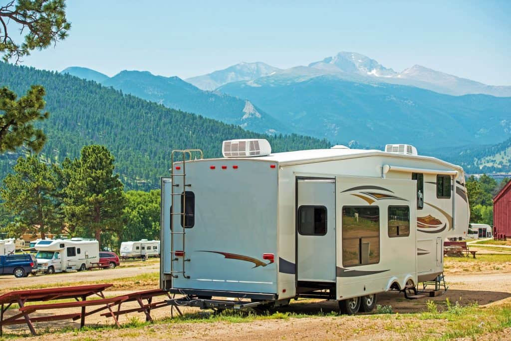 Fifth Wheel Camper at campground with mountains in background.