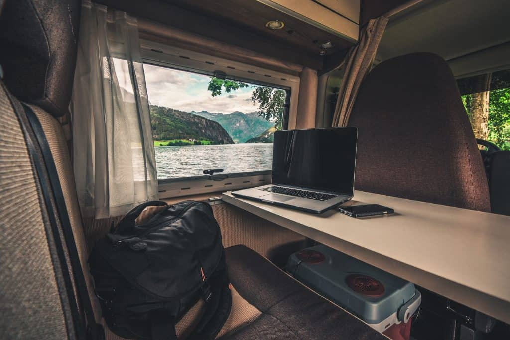 Laptop on table in camper van with scenic window view.