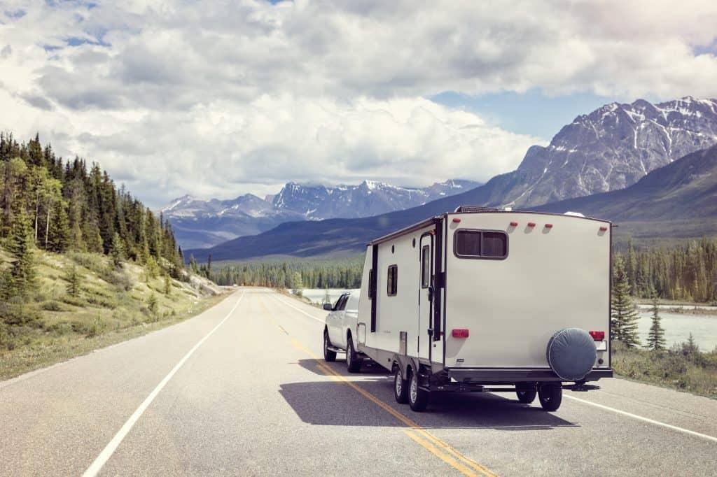 Pickup truck tows travel trailer on highway near Grand Tetons.