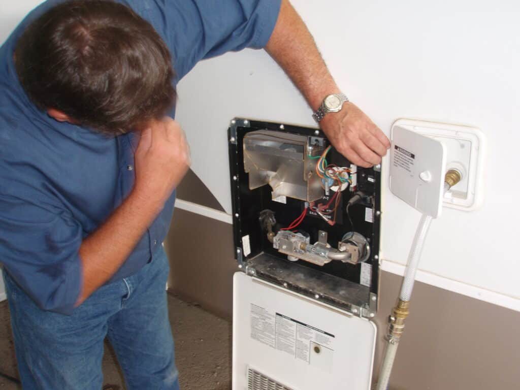 RVer inspecting an RV water heater vent.