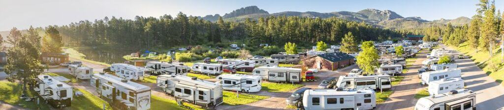 RVs scattered on sites in an RV park with mountains and trees surrounding.