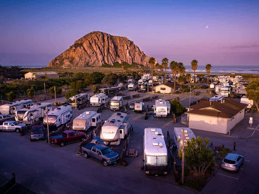 Rv park with RVs, vehicles, palm trees, ocean view with large rock formation