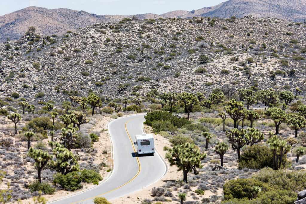 Small RV on winding road in remote area.