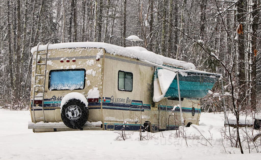 Old RV in woods covered with snow.