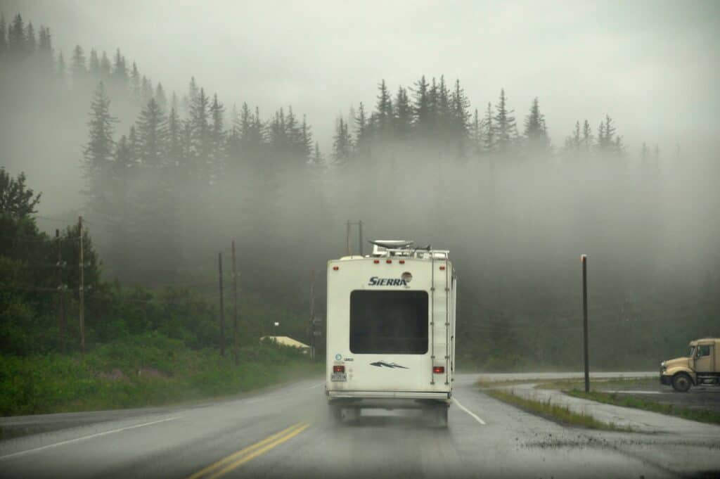 RV on highway surrounded by fog and rain.