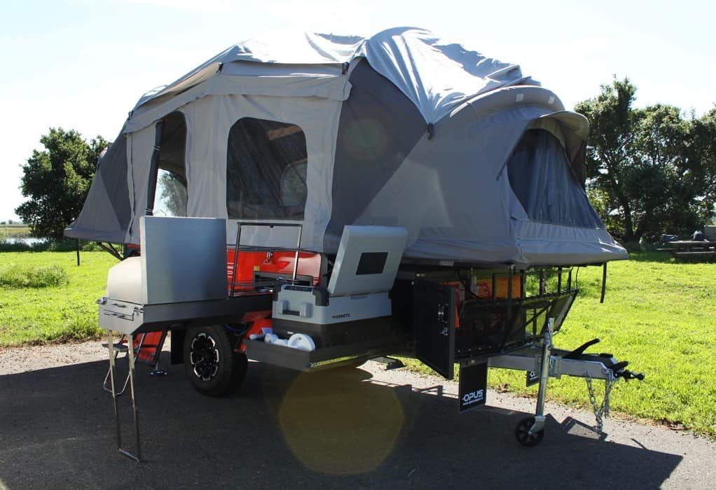 Opus camper fully extended and setup at campground.