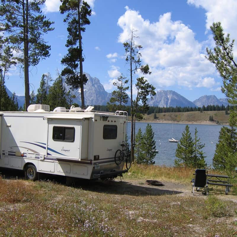 Motorhome at camp next to lake in mountainous area.