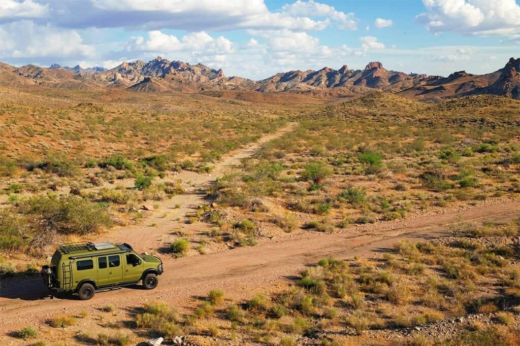 Camper van on dirt road in sparse public lands.