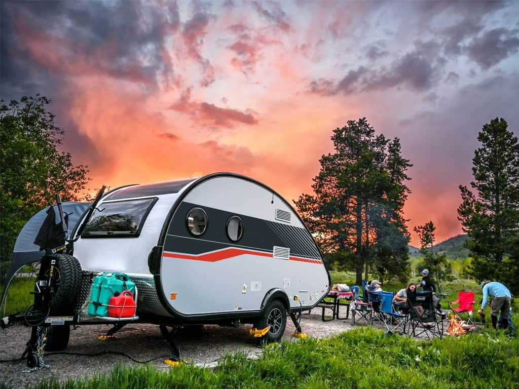 nuCamp travel trailer in rugged campsite with owners cooking over a fire.
