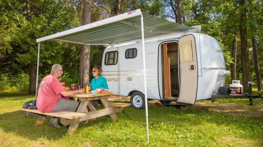 Couple enjoying outdoor meal near Scamp travel trailer.
