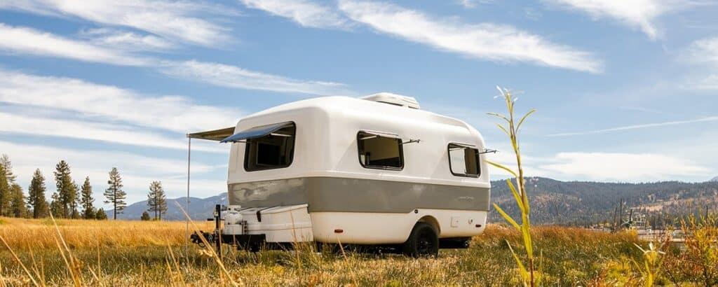 Small fiberglass travel trailer in remote field.