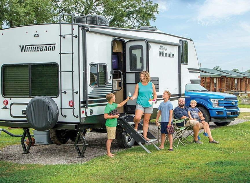 Family standing outside Winnebago Micro Winnie camper.