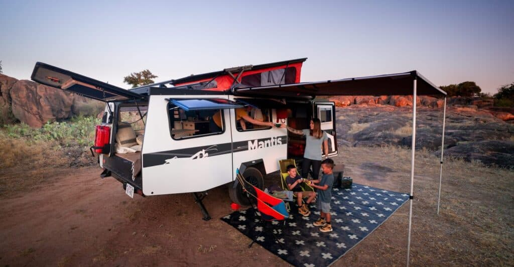 Taxa Mantis travel trailer setup at camp with family enjoying it.