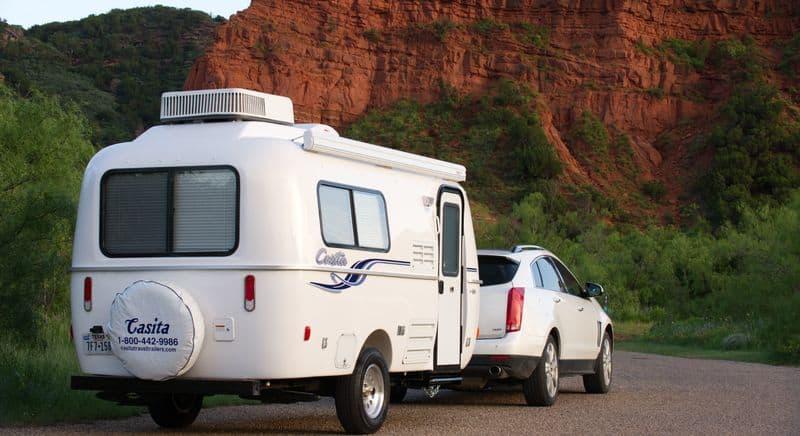 SUV tows Casita fiberglass camper near rocky canyon.
