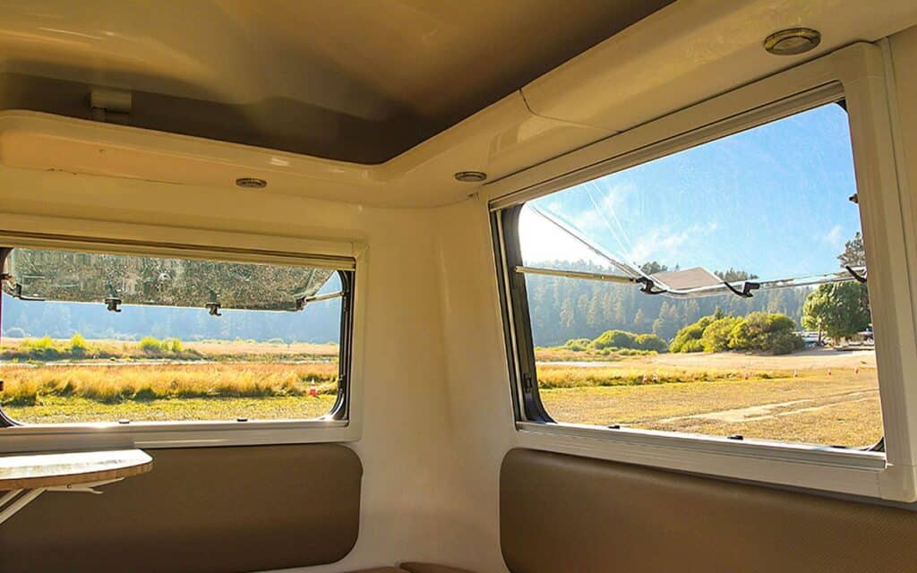 Interior of fiberglass camper with windows open.