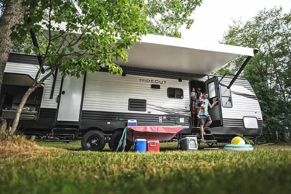 Family exits Keystone Hideout camper at campsite.