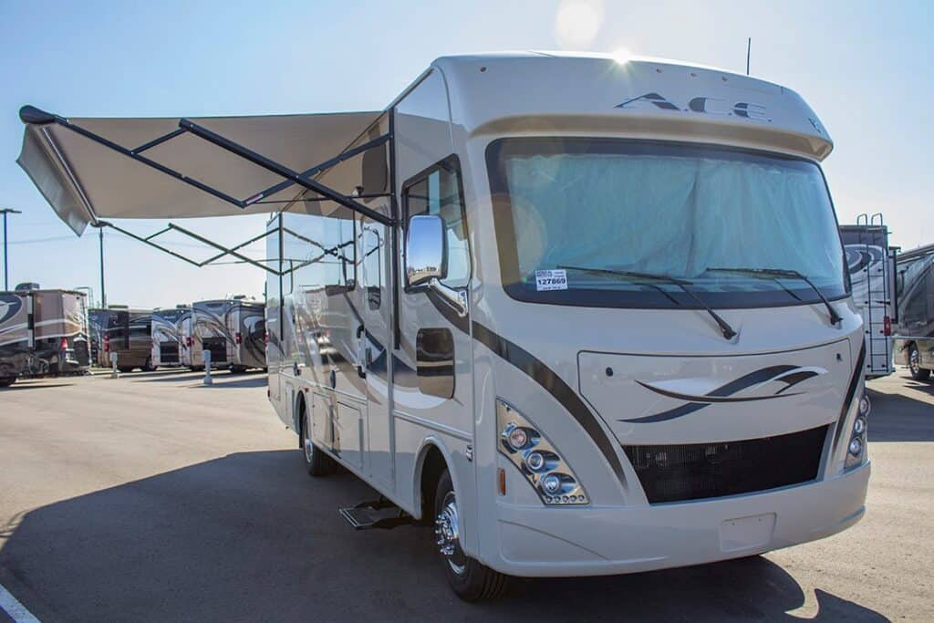 Class A RV for sale at dealer lot with awning extended.