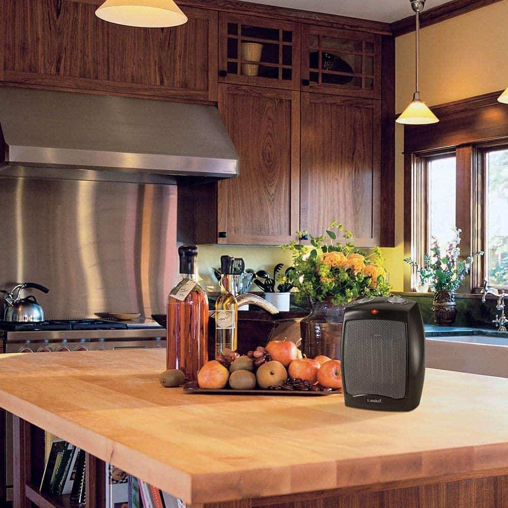 Electric heater sits on wooden kitchen countertop.