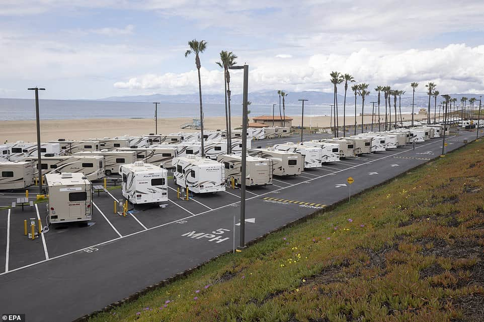 Class C RVs hooked up on beachside camping lot.