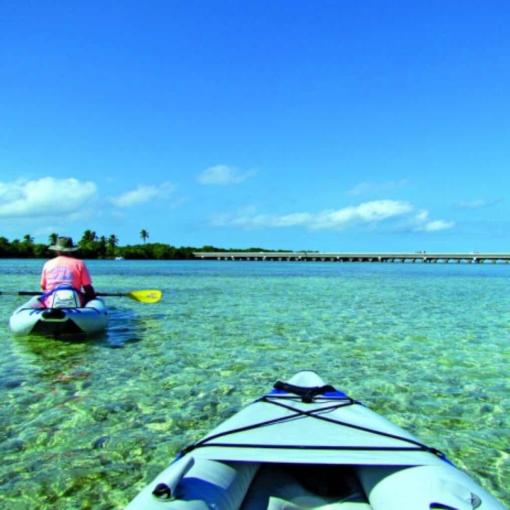Kayakers paddle through clear shallow water at Sunshine Key RV Resort.