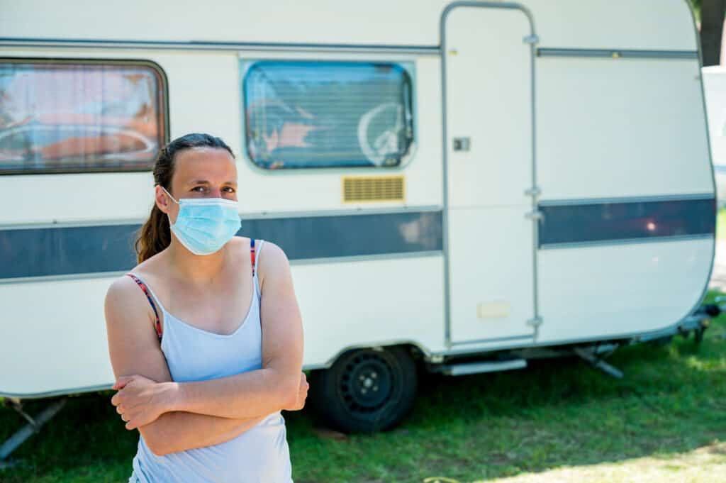 An RVer wears a mask at her campsite.
