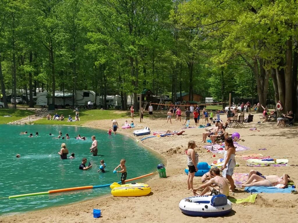 Campers enjoying the beach and swimming pond at Weidman KOA.