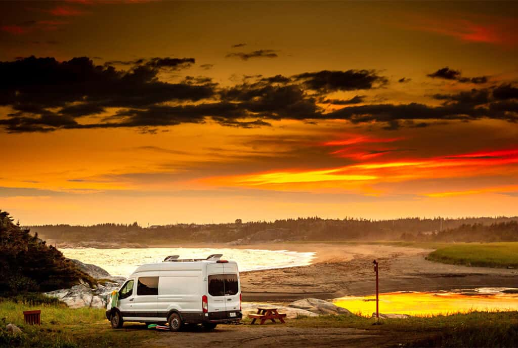 Class B van on scenic lakeside site at sunset.