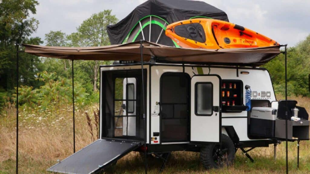 Forest River NoBo camper fully setup with tent and kayak on roof.