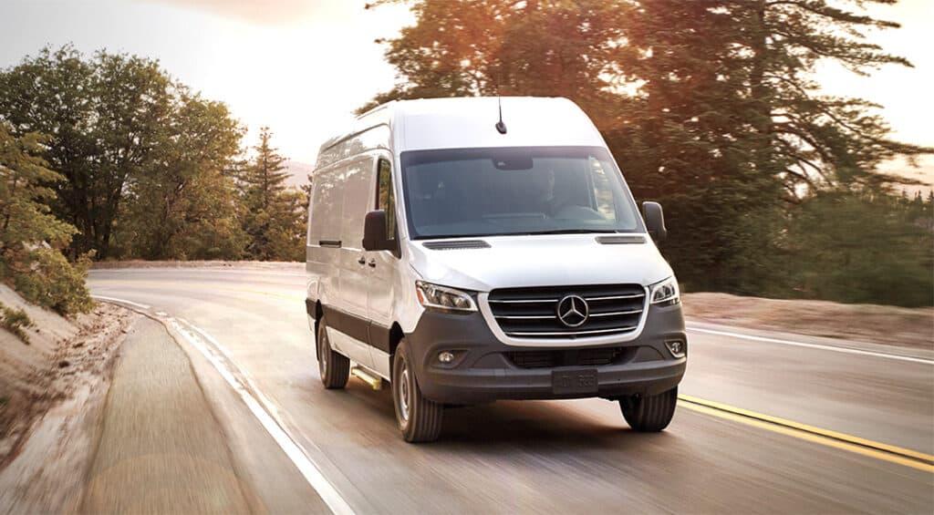 Mercedes Sprinter camper on scenic drive.