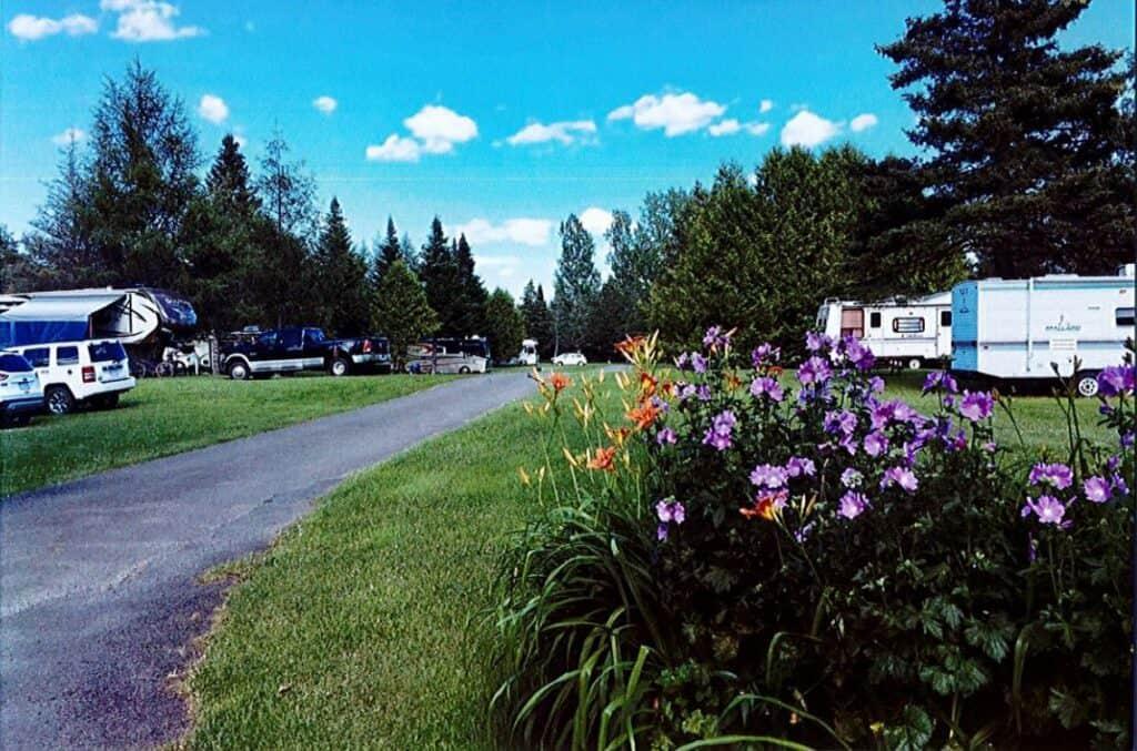 Houlton/Canadian Border KOA shows campsites and RVs amidst trees.