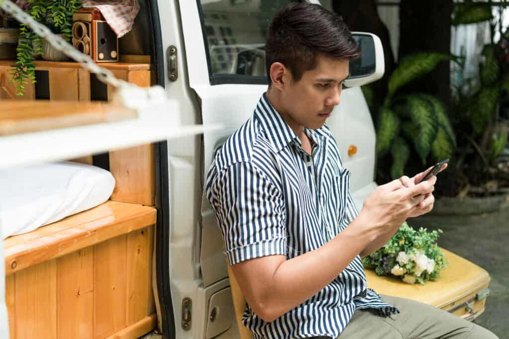 Man uses RV LIFE Pro on his mobile device while leaning on camper.