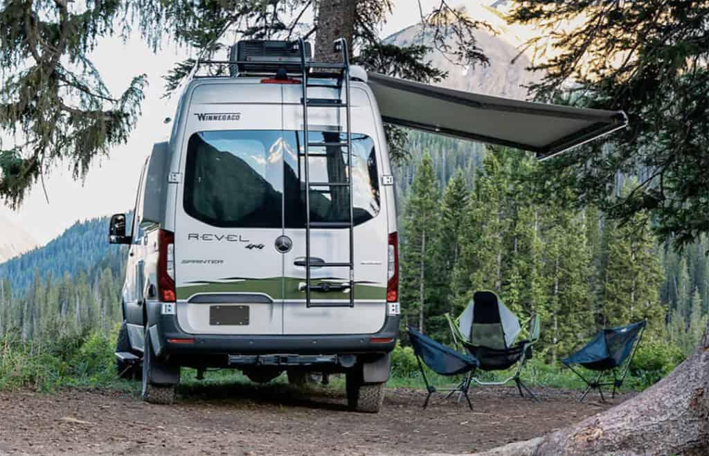Winnebago Revel camper fully setup in the forest.